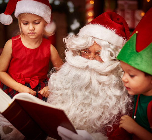 Santa reading a story to two small children