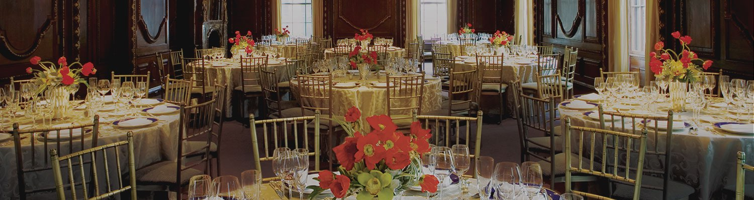 Room with brown wooden walls, red flower arrangements & tables with gold tablecloths & chairs