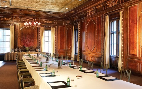 Large ballroom with long rectangular table, wooden walls & marble ceiling