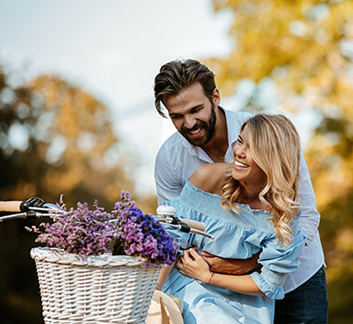 woman is on a bike with a basket of purple flowers while her man hugs her from behind
