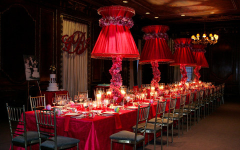 Long table with red tablecloth and chairs