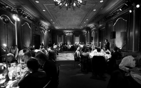 Black and white photo of people eating in drawing room