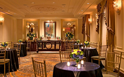 Dining space with round tables with purple tablecloths & golden window curtains
