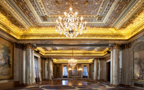 Big ballroom with marble columns, crystal chandeliers & golden accents on ceiling