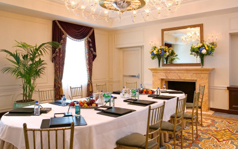 Meeting room with fireplace & large oval table set with notebooks, water bottles &snacks