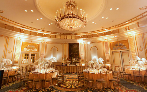 Ballroom with tables, chairs, and tall white flower centerpieces and a chandelier hanging in the middle of the ceiling