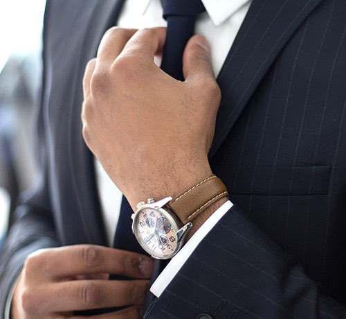 Close up of Man's hand wearing a high end wrist watch and suit and adjusting his tie Inset