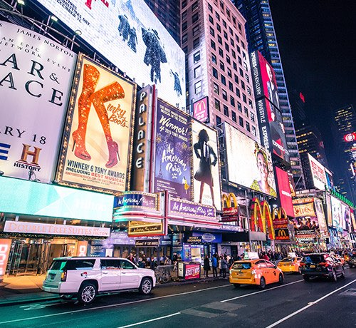 Digital theater signs in New York City lit up at night Inset