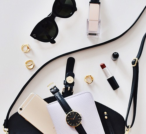 Gold cuff links, black sunglasses, black watch, lipstick and black purse on white background Inset