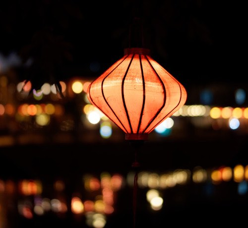 An orange chinese lantern lit up at night Inset