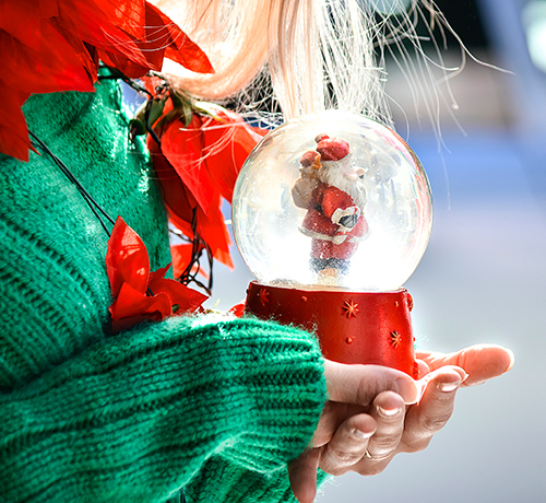 little girl in aa green sweater is holding a snowglobe with Santa inside of it  Inset