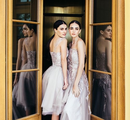 Two Women in formal silver dresses standing in a wooden framed doorway Inset