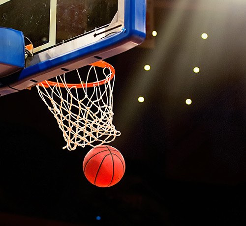 A basketball going through a basketball hoop against a black background Inset