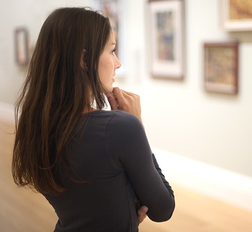 Woman with long brown hair and black shirt looking at paintings on a museum wall Inset