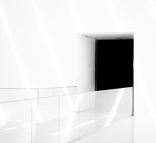 White walls, glass balcony leading into a black doorway Inset