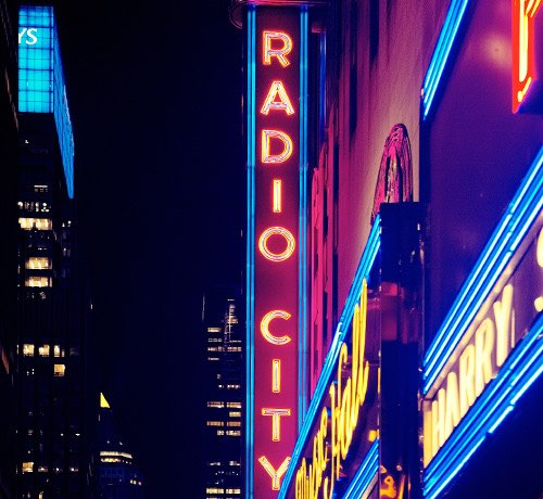 Radio City Music Hall sign lit up at night Inset