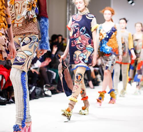 Woman in colorful outfits strutting down catwalk
