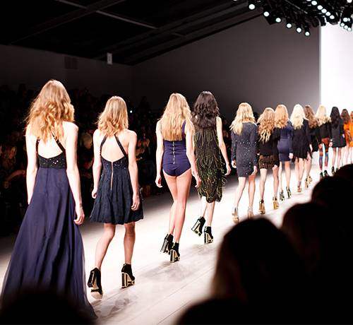 Line of women in muted color clothing strutting down catwalk