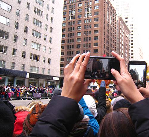 People holding cellphones up to record parade