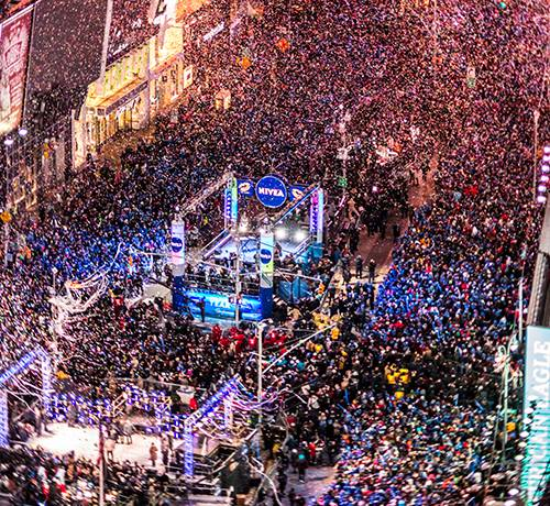 Birds eye view of times square at night with confetti falling and neon lights on