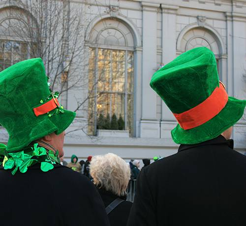 Two people wearing large green hats at the st. patricks parade
