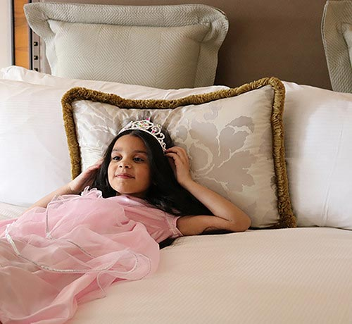 Girl in princess costume laying in bed