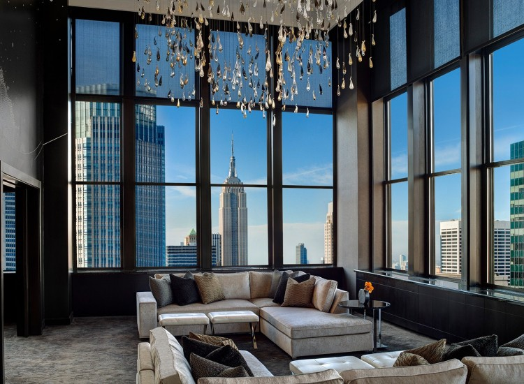 High ceiling, spacious living room with sofas, metallic chandelier & large window panel overlooking city view