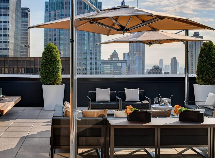 Rooftop terrace with seating, umbrellas & city view