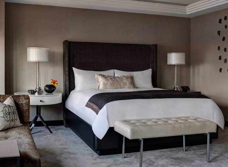 Champagne Suite guest room with king bed & white nightstands