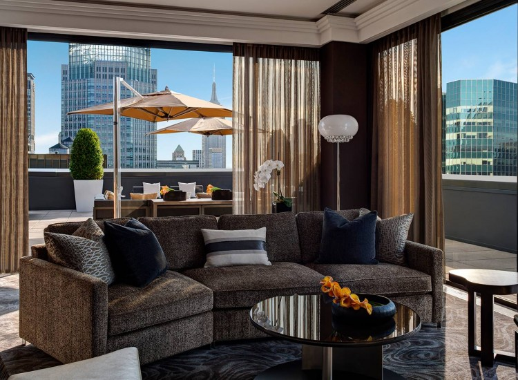 Champagne Suite living room with couches, tables & balcony door leading out to rooftop terrace