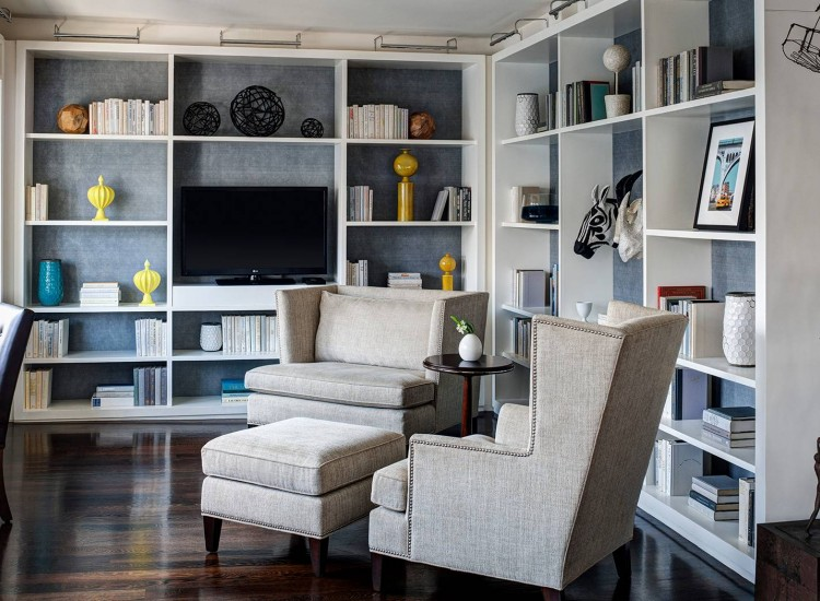Seating area with padded couch chairs & white wall shelving in the back with books & vases