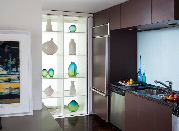 Full kitchen with shelving displaying variously shaped glass vases