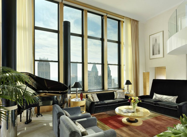 Living space with couches, coffee table, grand piano & large window panel with city view