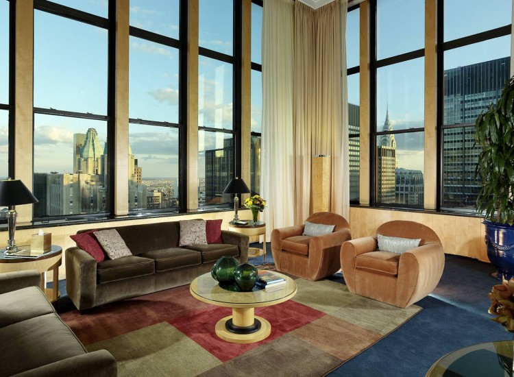 Cozy living space with couches, coffee table & large window panels with city view
