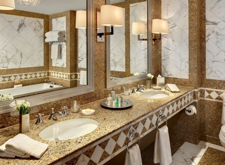Marble bathroom vanity with two sinks & white tub