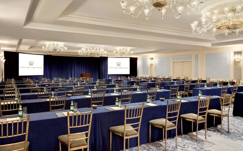 Large meeting room with long rectangular tables & chairs facing stage with two projection screens