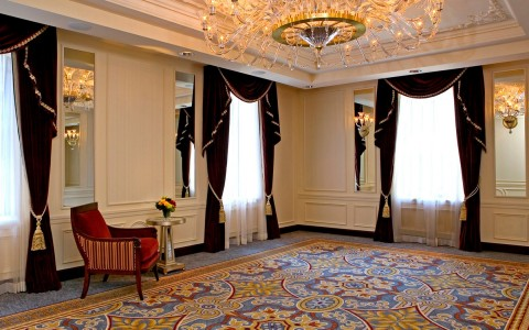 Large space with elegant chandelier & blue window curtains