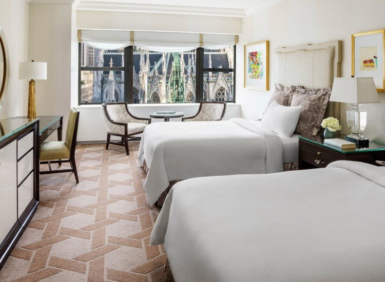 The Palace Rooms Cathedral Double guestroom with white linens and beautiful views of new york city
