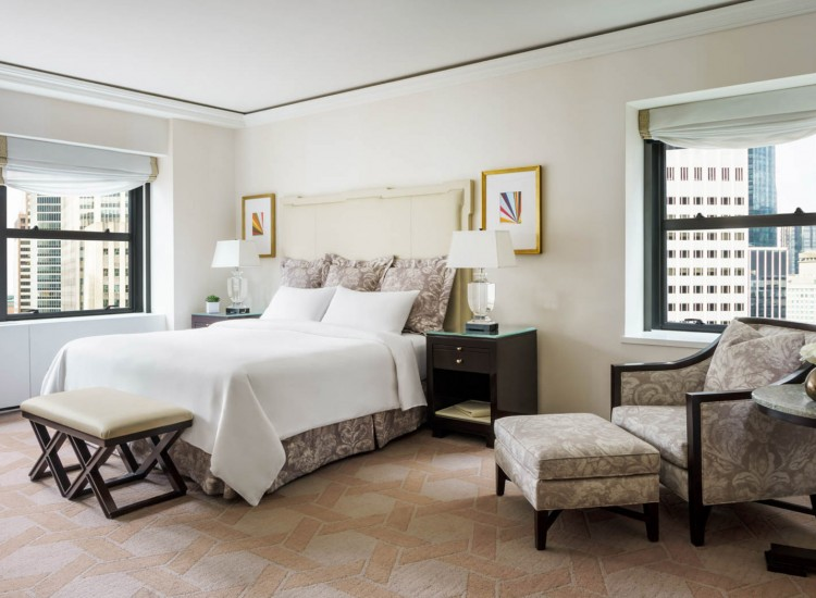 The Palace Deluxe Corner Suite guest room with king bed and views of new york city skyline
