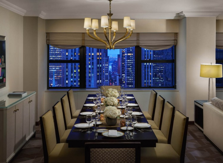 The Palace Deluxe Corner Suite dining room with eight seats and views of new york city at night
