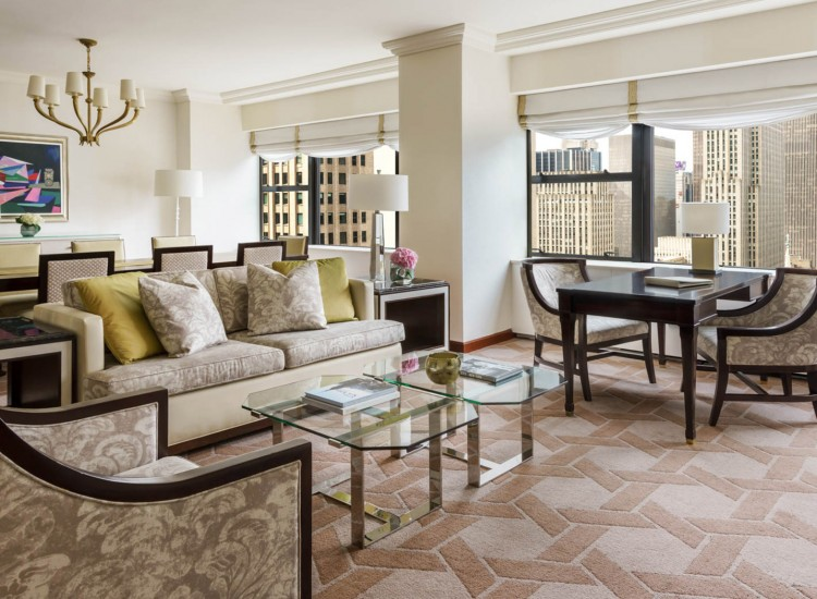 The Palace Deluxe Corner Suite living room with sofa and chairs and skyline views of new york city