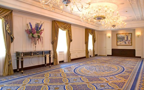 Large room with crystal chandeliers, golden window curtains & blue rug