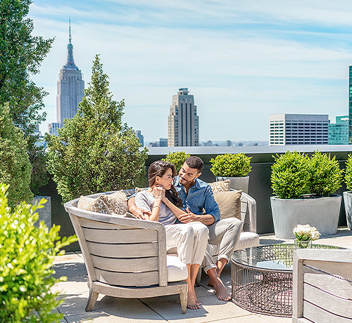 couple sitting in lounge chair cuddling on top of new york rooftop
