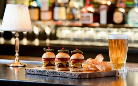 three burger sliders on bartop with a beer