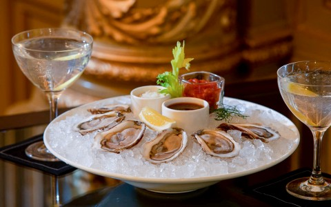 plate of raw oysters on ice with condiments