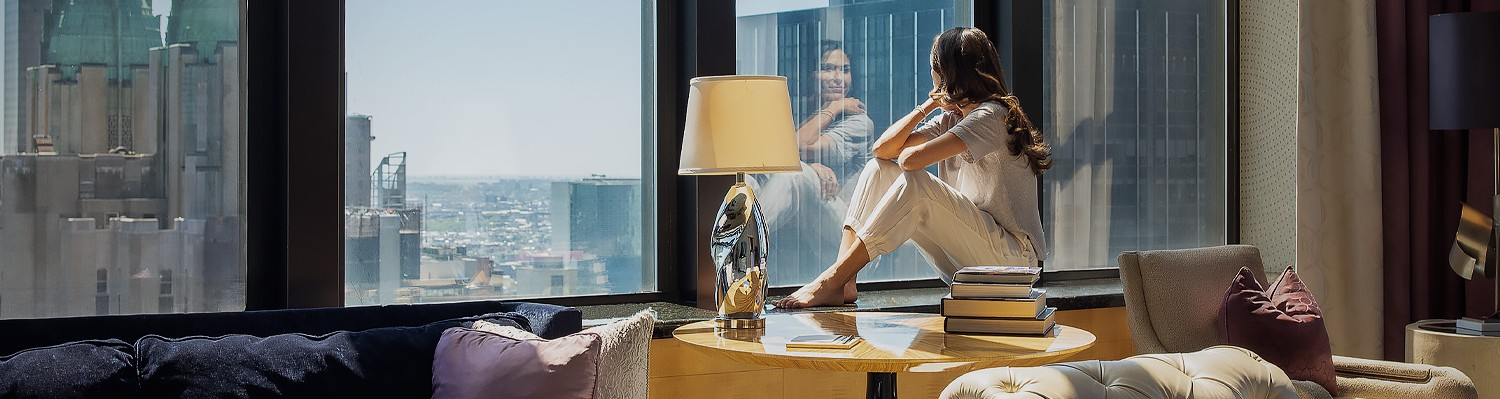 woman looking out the window in pajamas