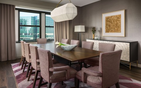 penthouse dining room with long wooden table and pink accent chairs