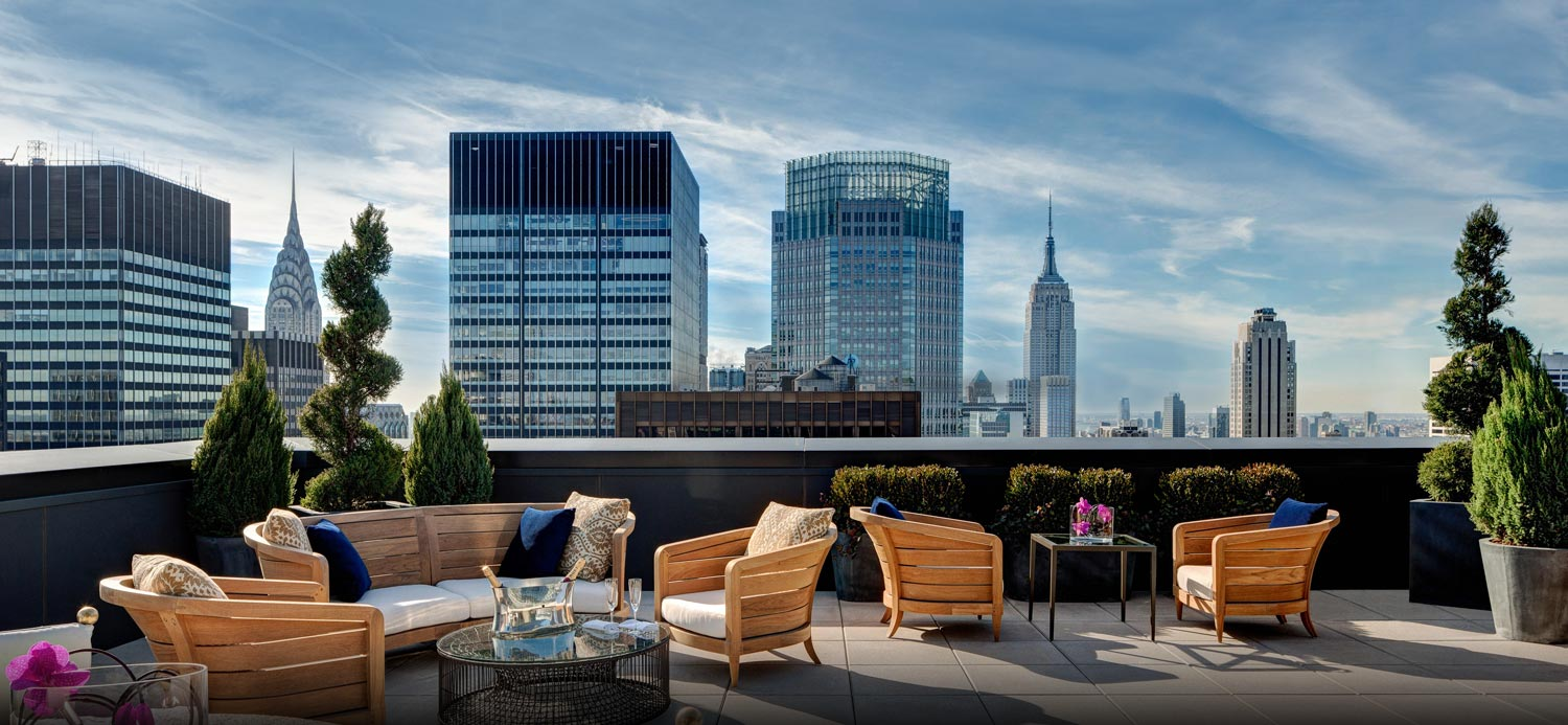Outdoor rooftop terrace with seating area & tall buildings in the back
