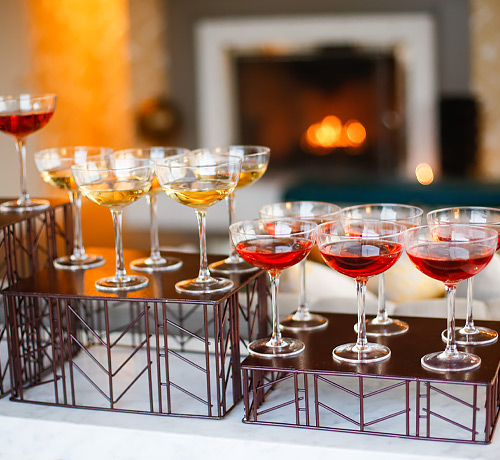 tiers of champagne flutes with red or yellow liquids