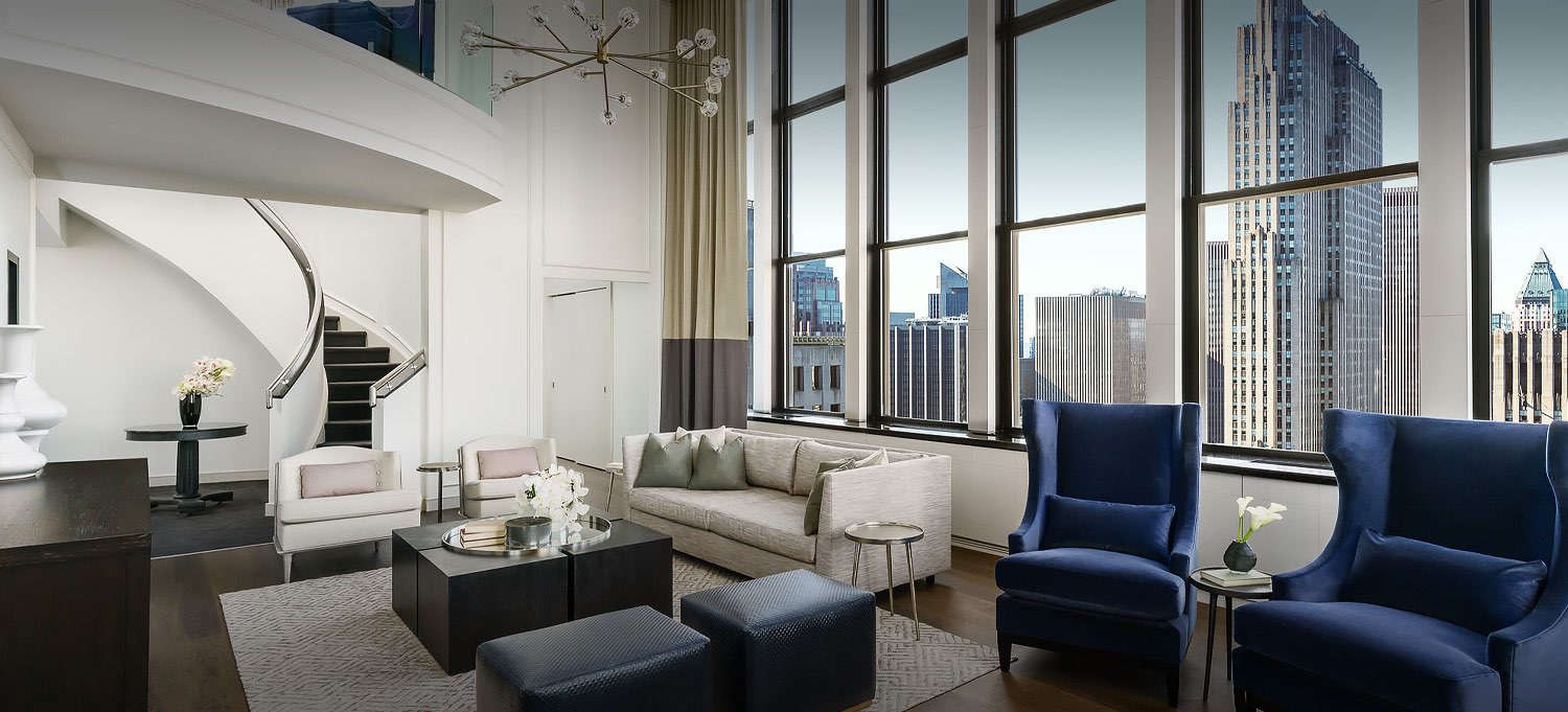 living room w white and blue couches and a view of the skyline